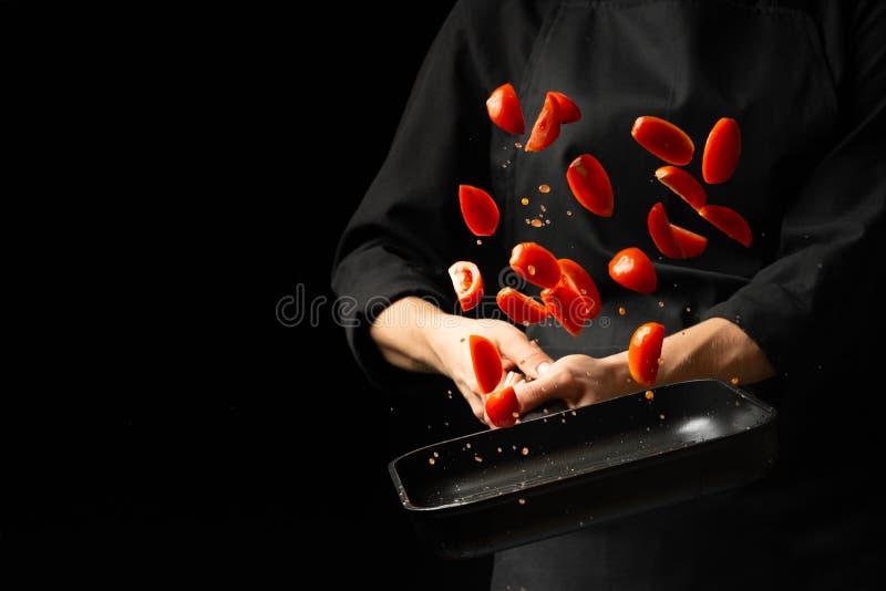 O cozinheiro chefe prepara o molho de tomate, frita os tomates, tomates de cereja em uma frigideira, gelo, para a massa, pizza as foto de stock royalty free