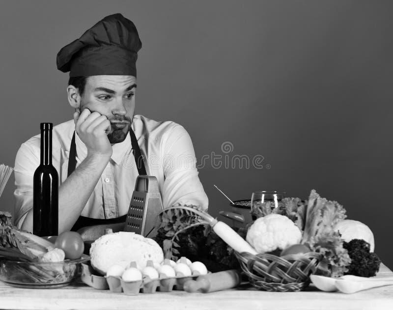 O cozinheiro chefe prepara-se O cozinheiro trabalha na cozinha perto da tabela com vegetais e ferramentas foto de stock