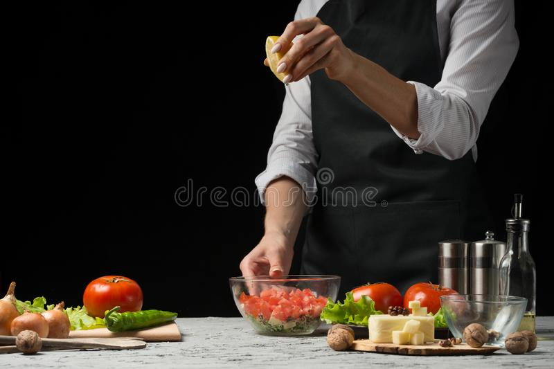 O cozinheiro chefe prepara uma salada, derrama o suco de limão em um fundo escuro com um espaço vazio para escrever imagens de stock