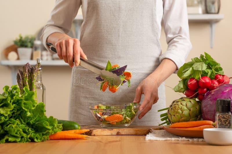 O cozinheiro chefe prepara uma salada fresca e brilhante, com vegetais em um fundo claro O conceito do alimento saudável e saudáv fotos de stock