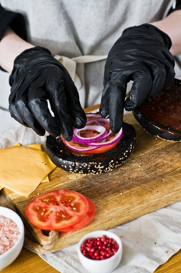 O cozinheiro chefe recolhe ingredientes de um cheeseburger r Receita caseiro do Hamburger imagens de stock