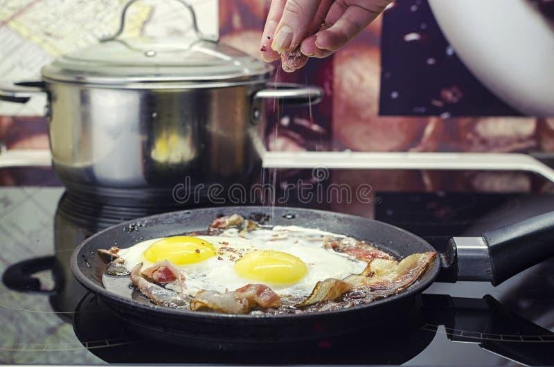 O cozinheiro chefe salga os ovos fritos em uma frigideira, cozinha o bacon e os ovos fritos na frigideira, cozinhando na cozinha, fotografia de stock