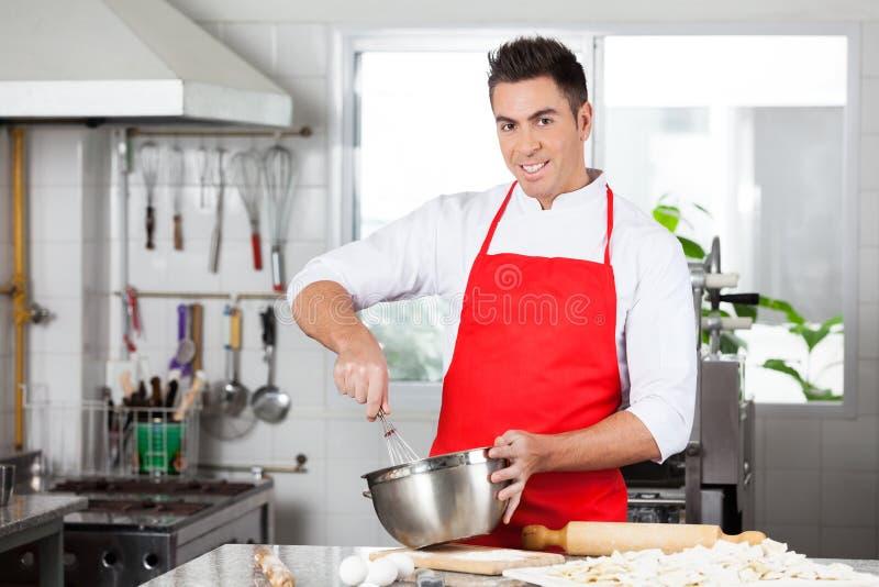 O cozinheiro chefe seguro Using Eggbeater To prepara o ravioli imagens de stock royalty free