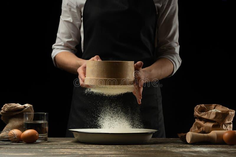 O cozinheiro chefe trabalha com farinha, para cozinhar o focaccia, a massa italiana, a pizza ou o pão Congelação no movimento Con foto de stock royalty free