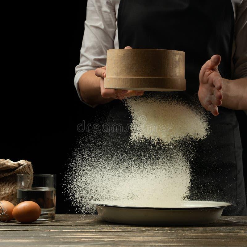 O cozinheiro chefe trabalha com farinha, para cozinhar o focaccia, a massa italiana, a pizza ou o pão Congelação no movimento Con imagem de stock