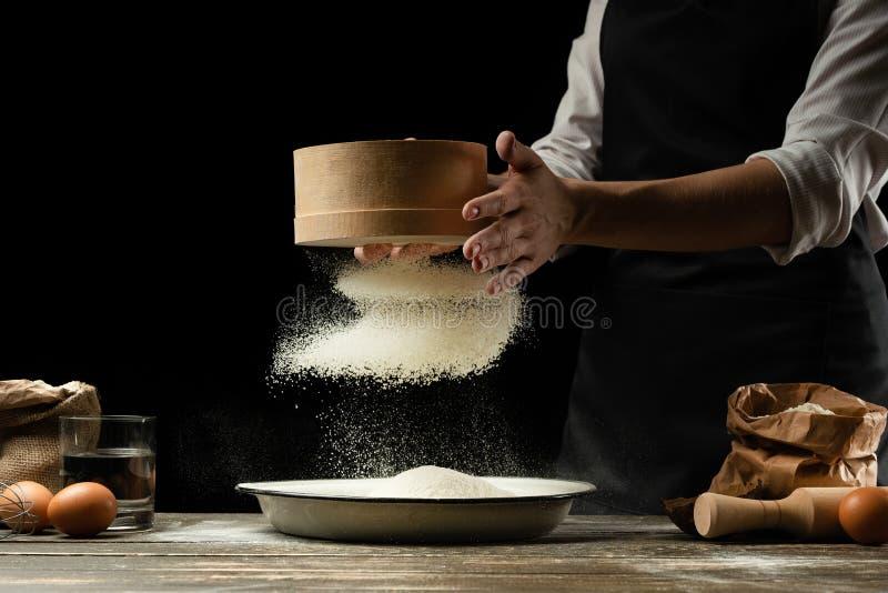 O cozinheiro chefe trabalha com farinha, para cozinhar o focaccia, a massa italiana, a pizza ou o pão Congelação no movimento Con imagem de stock royalty free