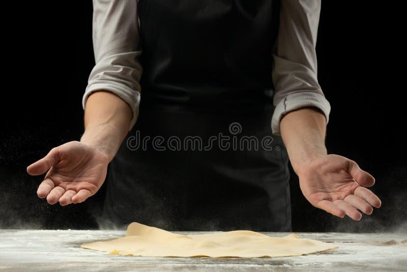 O cozinheiro chefe trabalha com massa, prepara a massa da pizza fotos de stock royalty free
