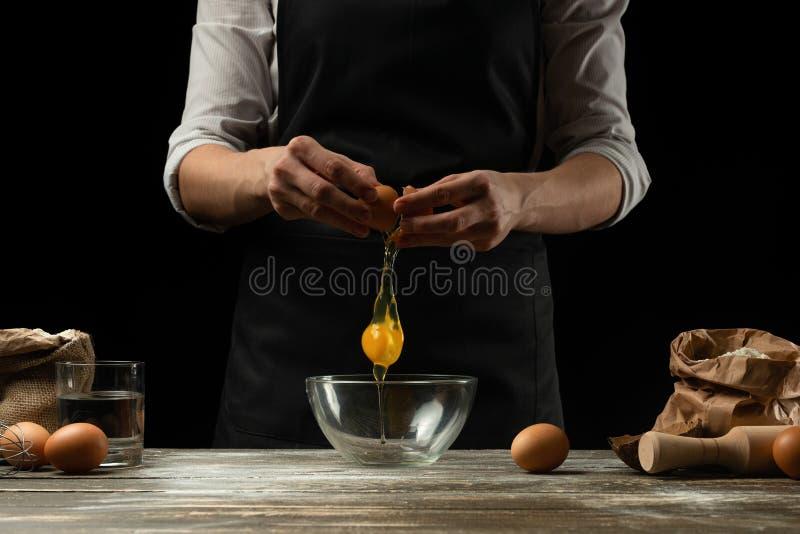 O cozinheiro chefe trabalha com massa, quebra o ovo e os chicotes, para a preparação do focaccia, da massa italiana, da pizza ou  fotografia de stock