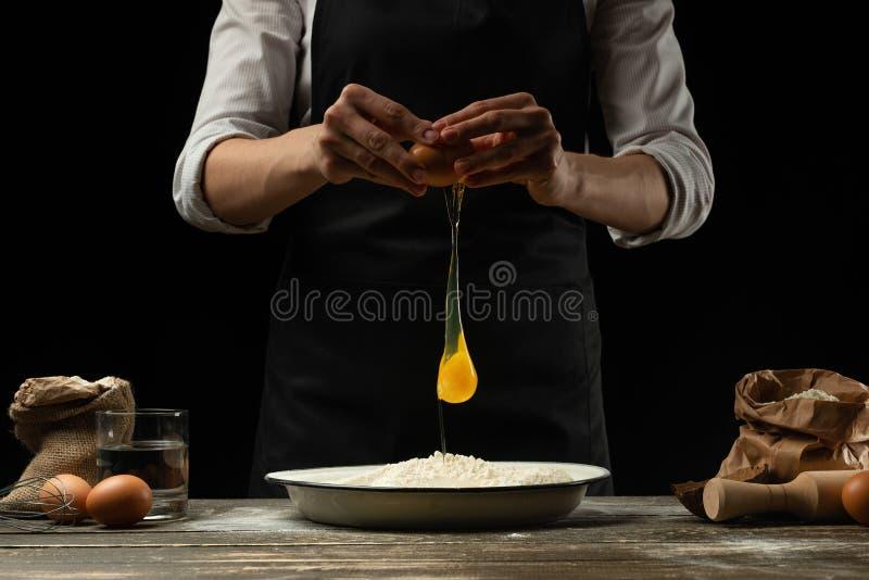 O cozinheiro chefe trabalha com massa, quebra o ovo e os chicotes, para a preparação do focaccia, da massa italiana, da pizza ou  foto de stock royalty free