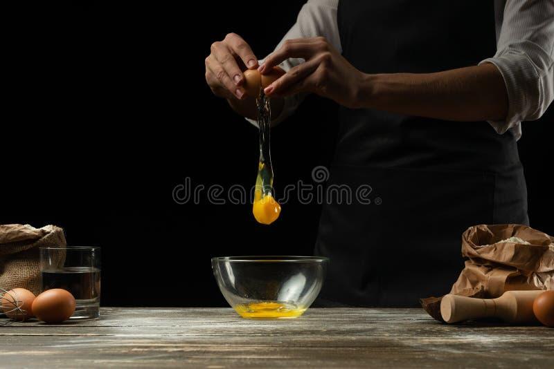 O cozinheiro chefe trabalha com massa, quebra o ovo e os chicotes, para a preparação do focaccia, da massa italiana, da pizza ou  foto de stock