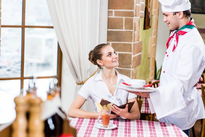 O cozinheiro chefe traz a um prato a mulher bonita em um restaurante fotografia de stock royalty free