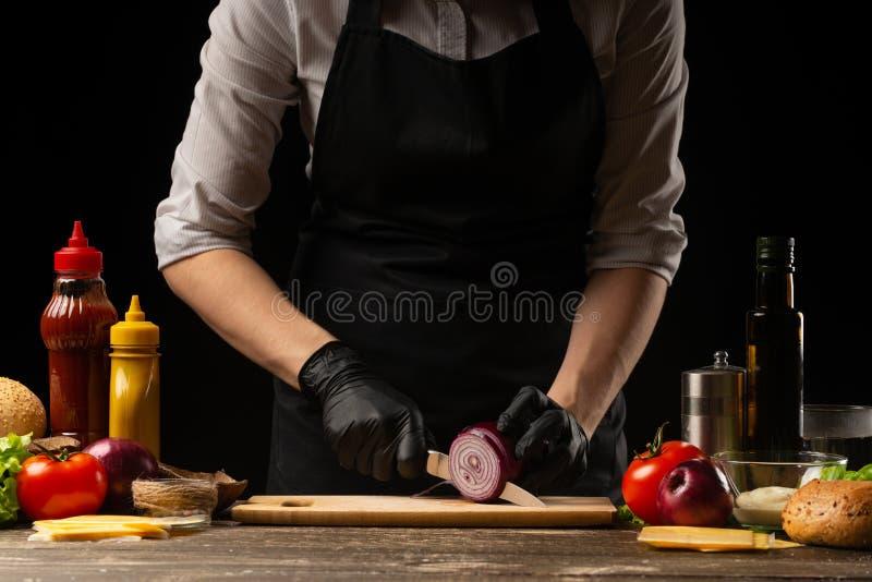O cozinheiro corta as cebolas vermelhas para pôr de conserva o hamburguer, a receita do hamburguer Cozinhando a receita, fazendo  imagens de stock royalty free