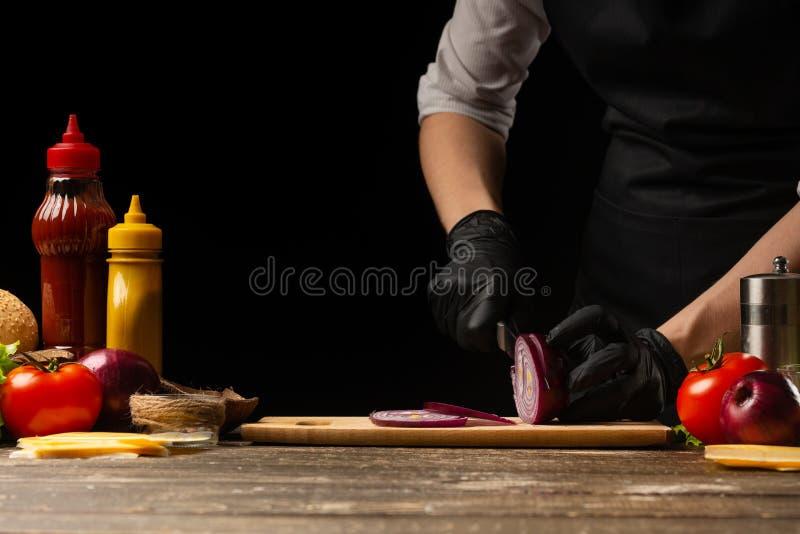 O cozinheiro corta as cebolas vermelhas para pôr de conserva o hamburguer, a receita do hamburguer Cozinhando a receita, fazendo  foto de stock royalty free