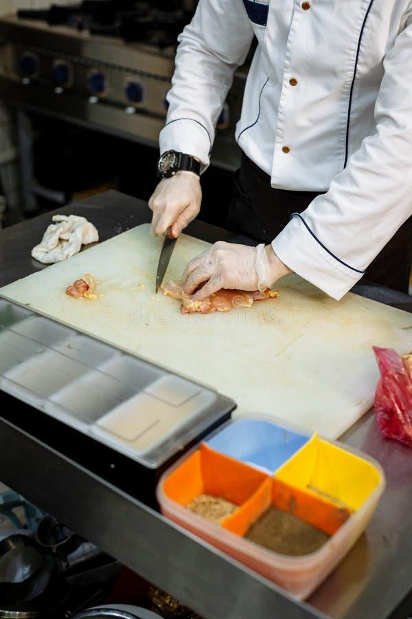 O cozinheiro corta a carne na placa branca ao lado da caixa com as especiarias na variedade foto de stock