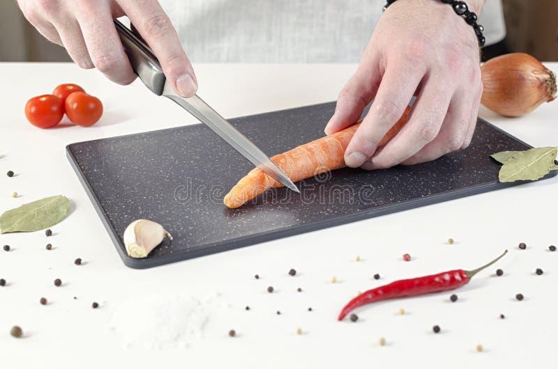 O cozinheiro corta a cenoura na placa de corte preta imagem de stock