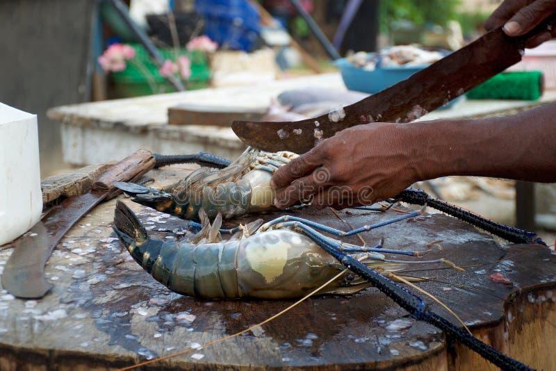 O cozinheiro cortou acima a lagosta no mercado de peixes foto de stock royalty free