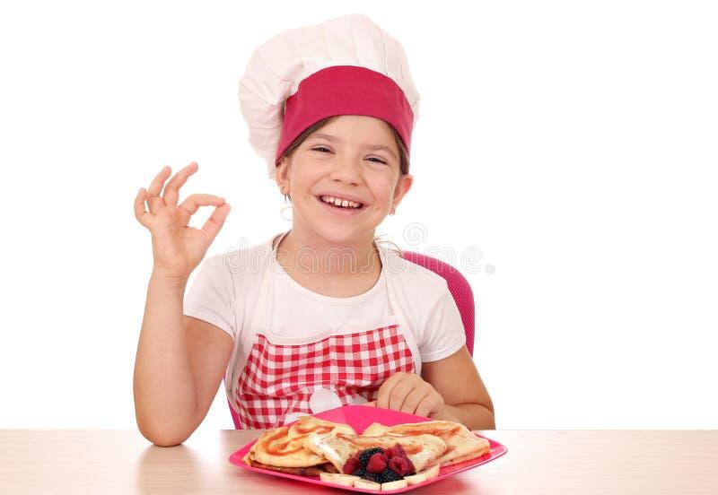 O cozinheiro da menina com crepes doces e a m?o aprovada assinam fotos de stock royalty free