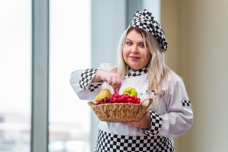 O cozinheiro da mulher que trabalha na cozinha brilhante fotografia de stock