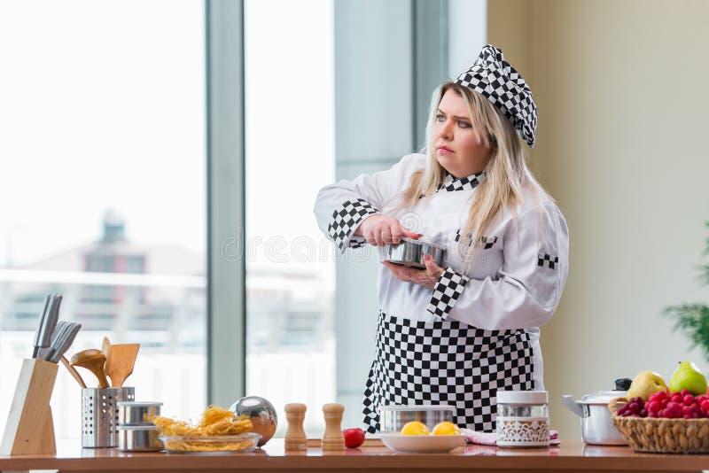 O cozinheiro da mulher que trabalha na cozinha brilhante fotos de stock royalty free