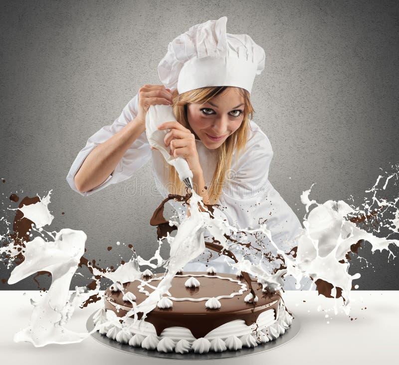 O cozinheiro de pastelaria prepara um bolo imagens de stock royalty free