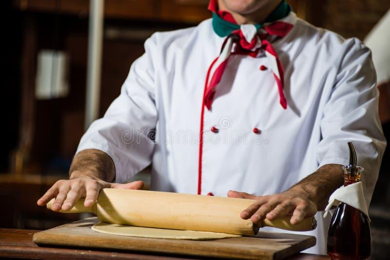 O cozinheiro desenrola a massa em uma placa fotografia de stock royalty free