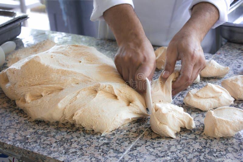 O cozinheiro do cozinheiro chefe trabalha com uma massa de fermento imagem de stock royalty free