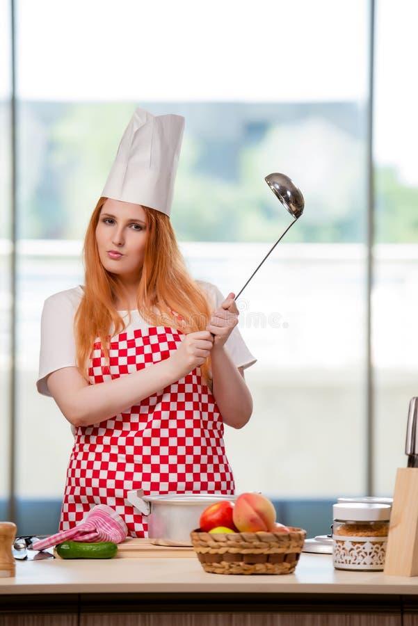 O cozinheiro do ruivo que trabalha na cozinha foto de stock