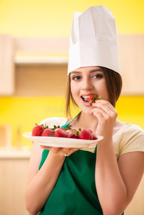 O cozinheiro fêmea novo que come morangos fotografia de stock royalty free