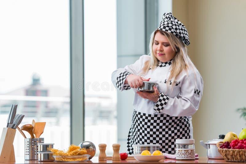 O cozinheiro fêmea que prepara a sopa na cozinha brilhantemente iluminada fotos de stock