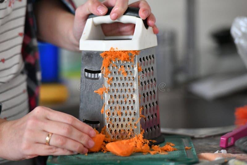 O cozinheiro fricciona cenouras em um ralador, um tipo da primeira pessoa fotos de stock royalty free