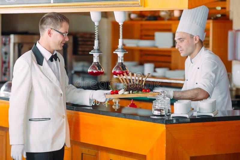 O cozinheiro passa ao garçom o prato terminado Cremalheira de cordeiro imagem de stock royalty free
