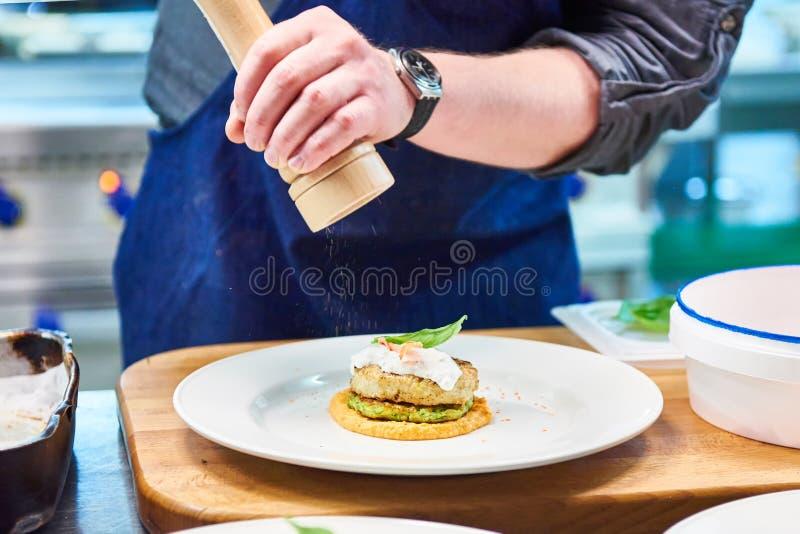 O cozinheiro polvilha o tempero no prato com a costoleta dos peixes no restaurante imagens de stock