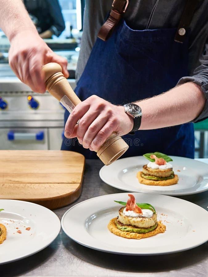 O cozinheiro polvilha o tempero no prato com a costoleta dos peixes no restaurante imagem de stock royalty free