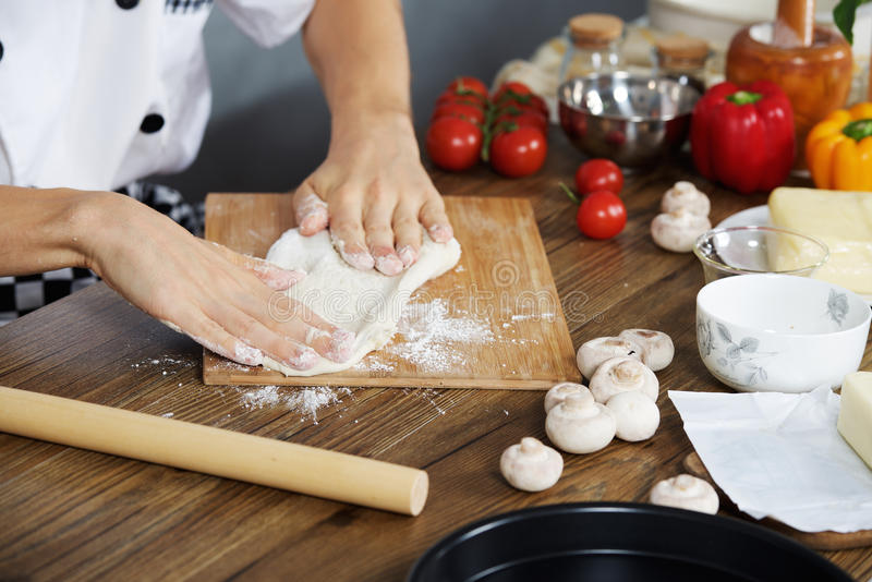 O cozinheiro prepara a massa da pizza imagens de stock