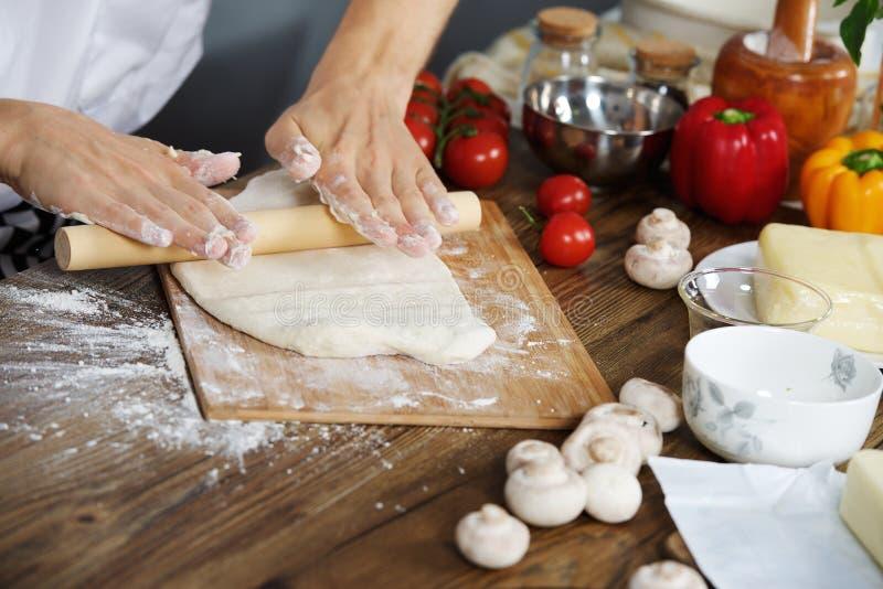 O cozinheiro prepara a massa da pizza fotos de stock royalty free