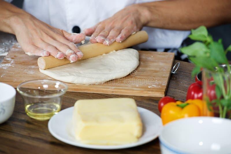 O cozinheiro prepara a massa da pizza fotos de stock