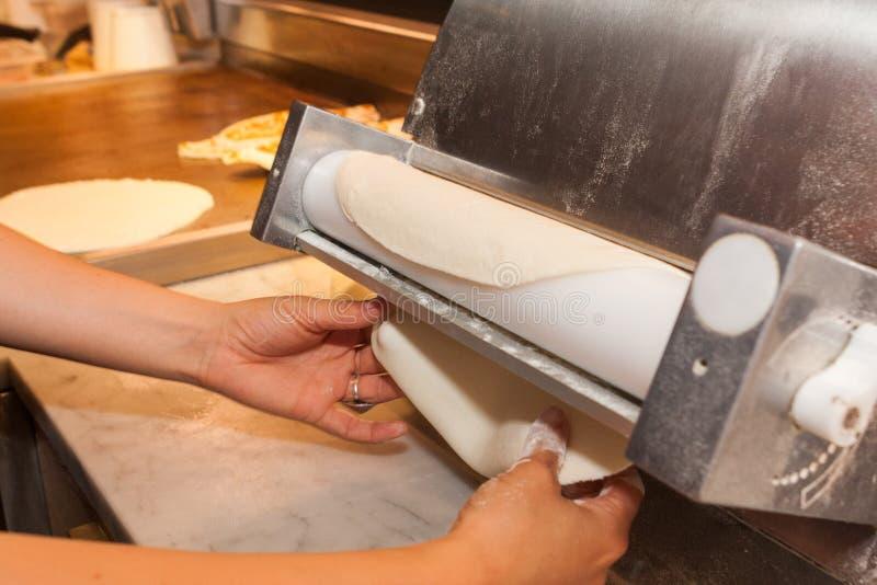 O cozinheiro principal rola a massa para a pizza com equipamento especial imagem de stock