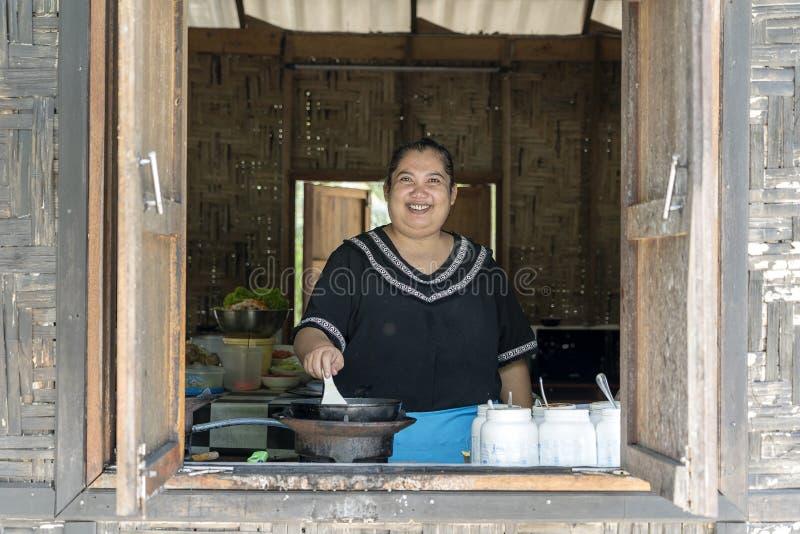 O cozinheiro tailand?s da mulher prepara pratos em um caf? da praia na ilha Koh Phangan, Tail?ndia Alimento tailand?s da rua, fim foto de stock