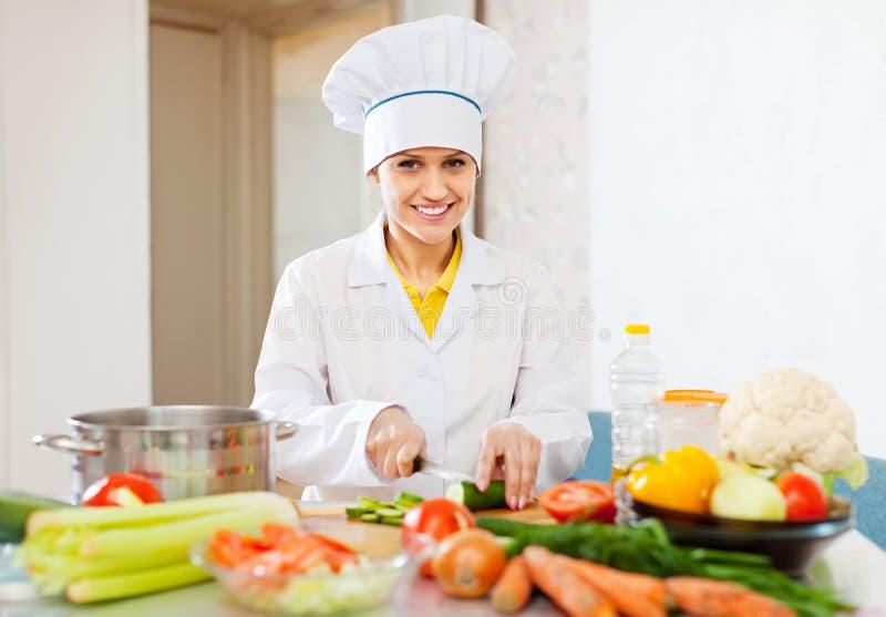 O cozinheiro trabalha com pepino e outros vegetais fotografia de stock