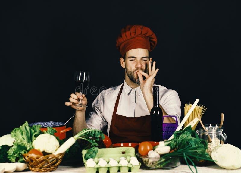 O cozinheiro trabalha na cozinha perto dos vegetais e das ferramentas Conceito italiano da bebida e do sommelier Homem no chapéu  fotos de stock