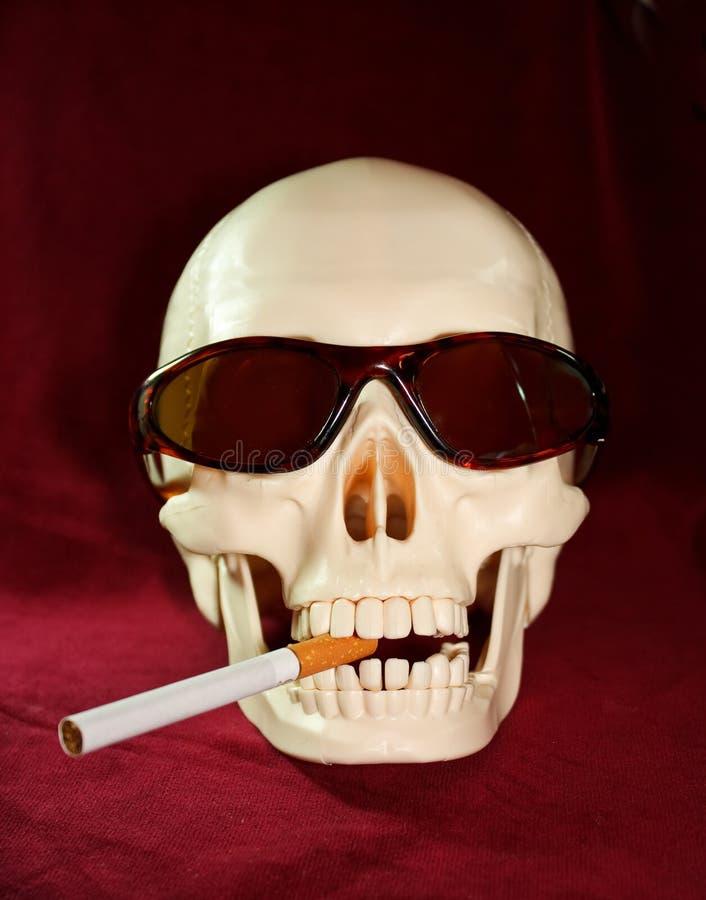 O crânio fuma um cigarro imagem de stock