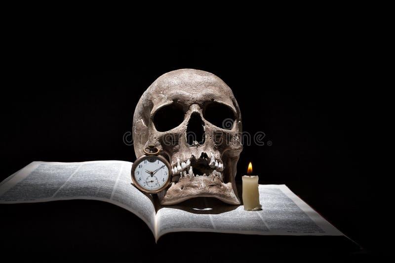 O crânio humano no livro aberto velho com vela ardente e o vintage cronometram no fundo preto sob o feixe de luz foto de stock