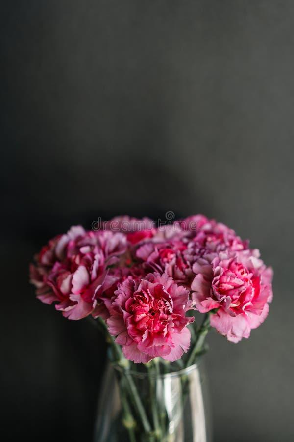 O cravo bonito floresce em um vaso em uma tabela Ramalhete da flor multicolorido violeta, roxa e cor-de-rosa Decoração de fotografia de stock