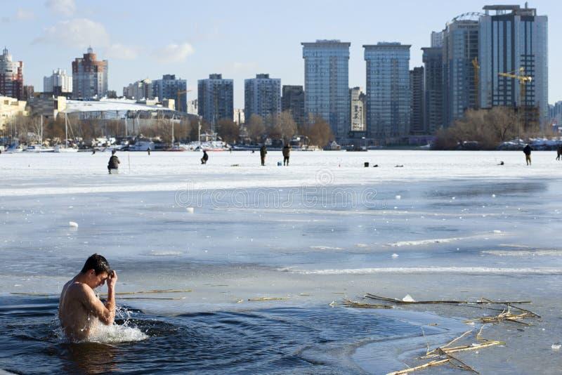 O crente ortodoxo está mergulhando em um furo do gelo na frente da arquitetura da cidade de Kyiv fotografia de stock