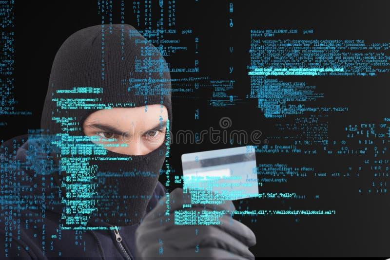 O criminoso do Cyber que veste uma capa está mantendo um cartão de crédito contra o fundo digital da chuva da matriz fotografia de stock