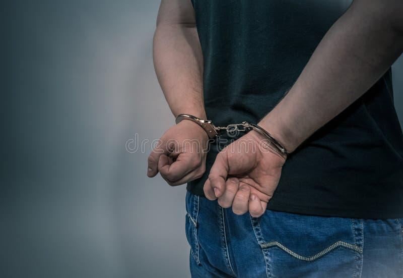 O criminoso prendido com as algemas atr?s de seu conceito de corpo para o crime n?o paga fotos de stock royalty free