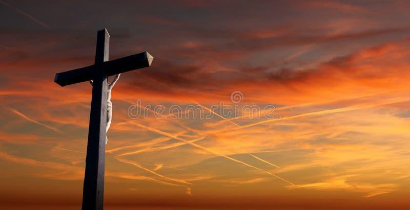 O cristão cruza sobre o fundo do por do sol imagens de stock