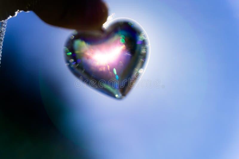 O cristal do coração refrata a luz solar - fundo do jardim de rosas imagem de stock