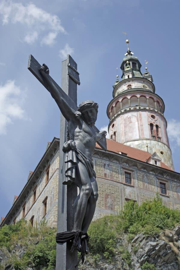 O Crucifix e um castelo elevam-se no krumlov cesky imagem de stock