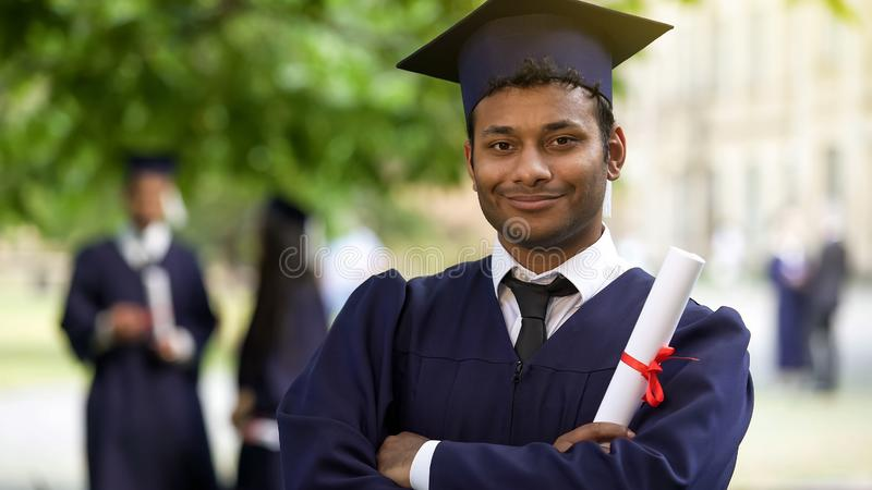 O cruzamento graduado sério arma-se com o diploma à disposição, conclusão do orgulho dos estudos imagens de stock